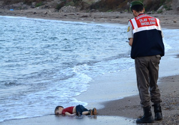 -- AFP PICTURES OF THE YEAR 2015 -- GRAPHIC CONTENT A Turkish police officer stands next to a migrant child's dead body (Aylan Shenu) off the shores in Bodrum, southern Turkey, on September 2, 2015 after a boat carrying refugees sank while reaching the Greek island of Kos. Thousands of refugees and migrants arrived in Athens on September 2, as Greek ministers held talks on the crisis, with Europe struggling to cope with the huge influx fleeing war and repression in the Middle East and Africa. AFP PHOTO / Nilufer Demir / DOGAN NEWS AGENCY = TURKEY OUT =