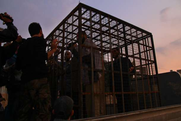 -- AFP PICTURES OF THE YEAR 2015 -- Syrians are seen inside a cage in Douma, the largest opposition stronghold on the outskirts of Damascus, on October 31, 2015, as it has been reported that a major Syrian rebel group is using dozens of captives in metal cages as
