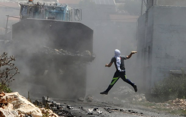 -- AFP PICTURES OF THE YEAR 2015 -- A Palestinian protester throws a bottle filled with paint at an Israeli army bulldozer during clashes following a demonstration against the expropriation of Palestinian land by Israel in the village of Kfar Qaddum, near Nablus in the occupied West Bank, on August 21, 2015. AFP PHOTO / JAAFAR ASHTIYEH