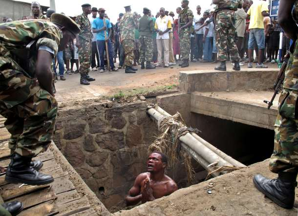 -- AFP PICTURES OF THE YEAR 2015 -- A man begs for help from the military as he stands in a drain where he had hid himself to escape a lynching by a mob at the Cibitoke district of Burundi capital, Bujumbura on May 7, 2015. The man suspected to be an 'Imbonerakure', or member of the Youth League of Burundi's ruling party was finally saved by the army. At least three people were killed in clashes in Burundi in protests over the president's bid for a third term. AFP PHOTO / Aymeric VINCENOT