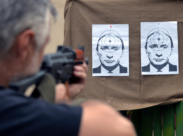 Soldado ucraniano atira em alvo com a cara do presidente russo, enquanto a tensão entre os dois países se intensifica (Imagem: AFP)