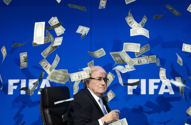 -- AFP PICTURES OF THE YEAR 2015 -- FIFA president Sepp Blatter looks on as fake dollar notes fly around him, thrown by a British comedian during a press conference at the FIFA world-body headquarter's on July 20, 2015 in Zurich. The 79-year-old Swiss official looked shaken as the notes thrown by Simon Brodkin, stagename Lee Nelson, fluttered around him in a conference hall at the FIFA headquarters. Brodkin was taken away in a Swiss police car after the stunt. AFP PHOTO / FABRICE COFFRINI