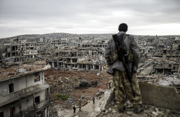 -- AFP PICTURES OF THE YEAR 2015 -- Musa, a 25-year-old Kurdish marksman, stands atop a building as he looks at the destroyed Syrian town of Kobane, also known as Ain al-Arab, on January 30, 2015. Kurdish forces recaptured the town on the Turkish frontier on January 26, in a symbolic blow to the jihadists who have seized large swathes of territory in their onslaught across Syria and Iraq. AFP PHOTO/BULENT KILIC