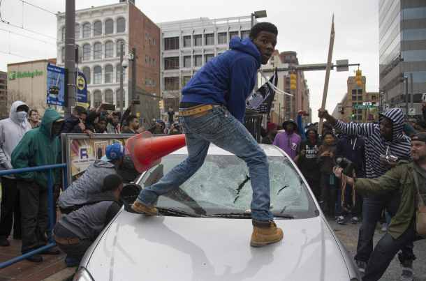 -- AFP PICTURES OF THE YEAR 2015 -- Demonstrators destroy the windshield of a Baltimore Police car as they protest the death Freddie Gray, an African American man who died of spinal cord injuries in police custody, in Baltimore, Maryland, April 25, 2015. Protesters returned to Baltimore's streets Saturday to vent outrage over the death of Gray on April 12. AFP PHOTO/JIM WATSON