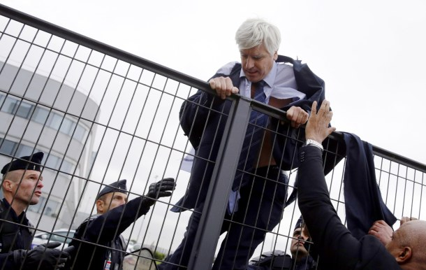 -- AFP PICTURES OF THE YEAR 2015 -- Director in charge of human resources of Air France long-haul flights, Pierre Plissonnier, nearly shirtless, is helped by security and police officers to climb over a fence, after several hundred employees stormed into the offices of Air France, interrupting the meeting of the Central Committee (CCE) in Roissy-en-France, on October 5, 2015. Air France-KLM unveiled a revamped restructuring plan on October 5 that could lead to 2,900 job losses after pilots for the struggling airline refused to accept a proposal to work longer hours. AFP PHOTO / KENZO TRIBOUILLARD