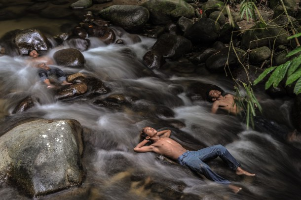 -- AFP PICTURES OF THE YEAR 2015 -- Malaysian youths cool off in a river as schools remain closed due to hazy conditions in Hulu Langat on October 6, 2015. Malaysia, Singapore and large expanses of Indonesia have suffered for weeks from acrid smoke billowing from fires on Indonesian plantations and peatlands that are being illegally cleared by burning. The regional environmental crisis has caused flights and major events to be cancelled, and forced tens of thousands of people in the region to seek medical treatment for respiratory problems. AFP PHOTO / MOHD RASFAN